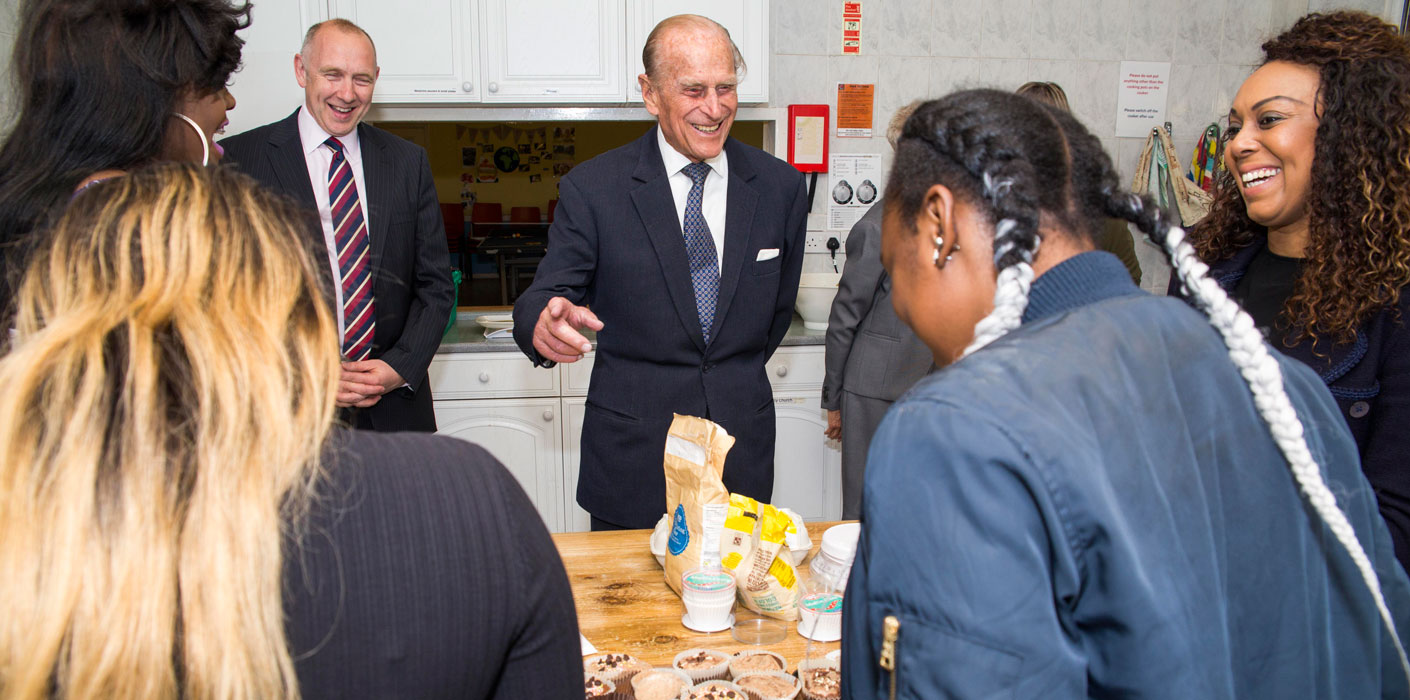 The Duke of Edinburgh laughs with people gathered around a kitchen table