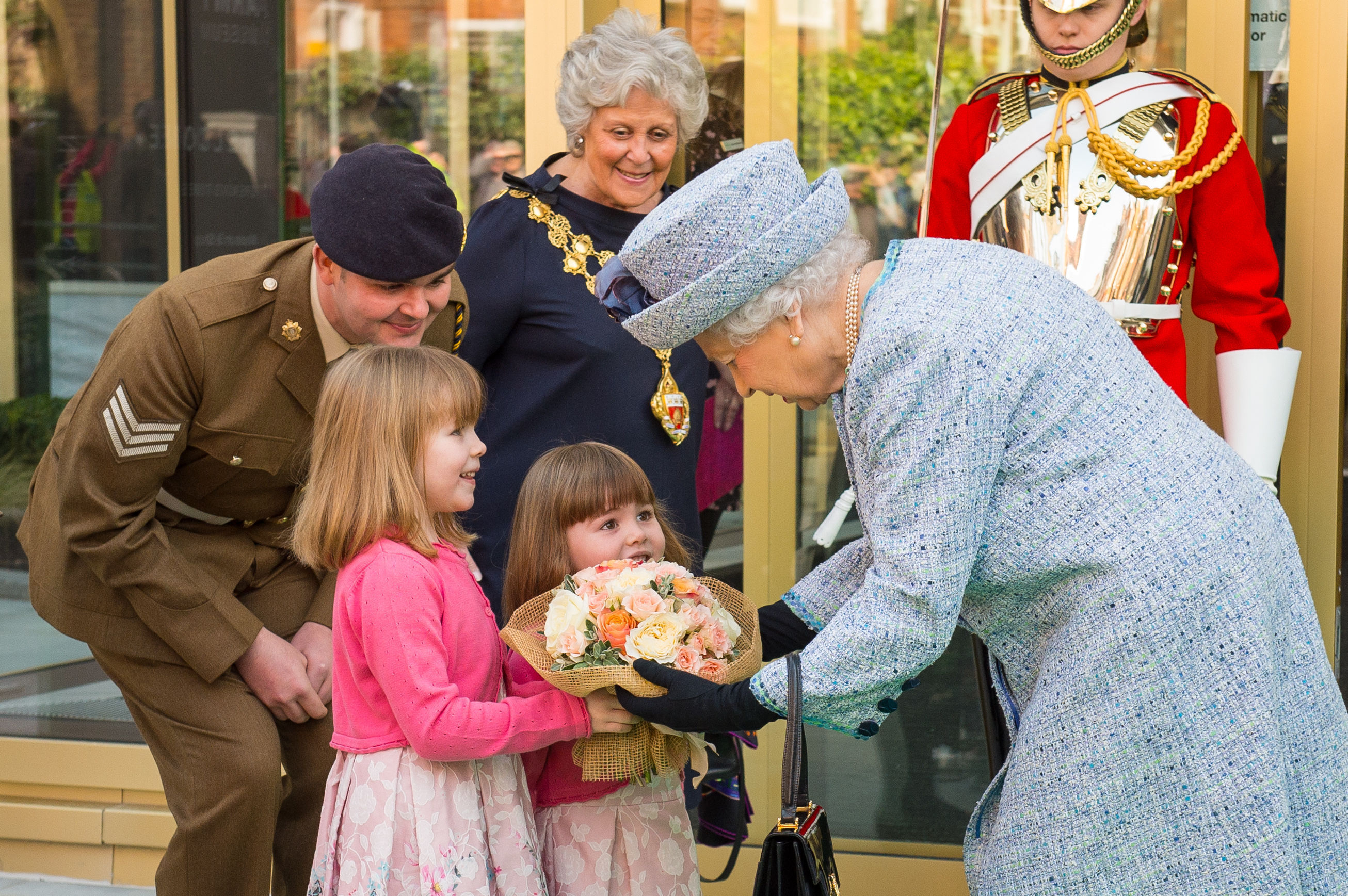 The Queen is presented with a posy after reopening the National Army Museum