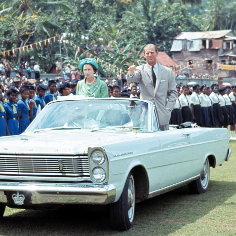 The Queen and The Duke of Edinburgh are driven towards a children's rally in St. Lucia in 1966.