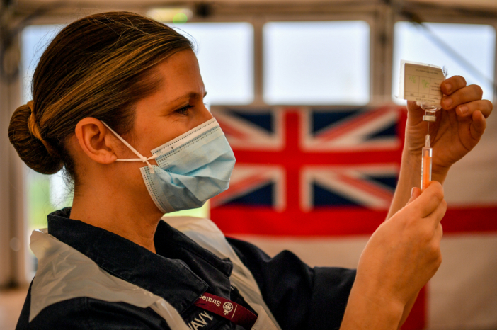 A nurse holds up a syringe in front of a Union Jack flag